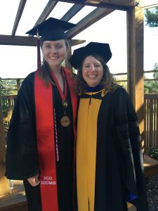 Student and faculty in graduation garb