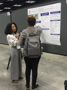 Student Michelle presenting poster at conference version 2